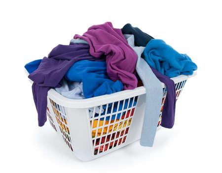 ropa casual: Ropa brillante en una canasta de lavander�a sobre fondo blanco. Azul, �ndigo, p�rpura.  Foto de archivo