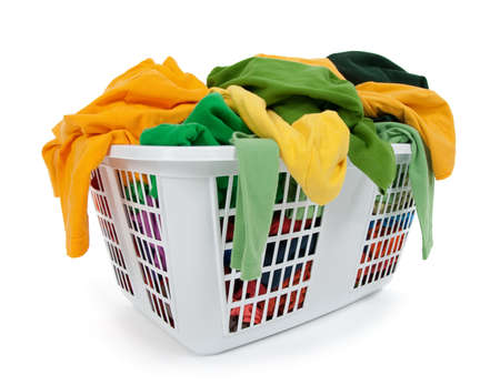 basket: Bright clothes in a laundry basket on white background. Green, yellow. Stock Photo