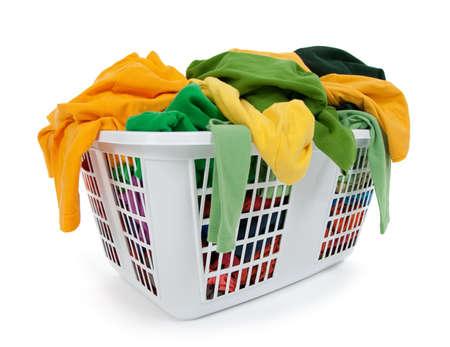 ropa casual: Ropa brillante en una canasta de lavander�a sobre fondo blanco. Verde, amarillo.