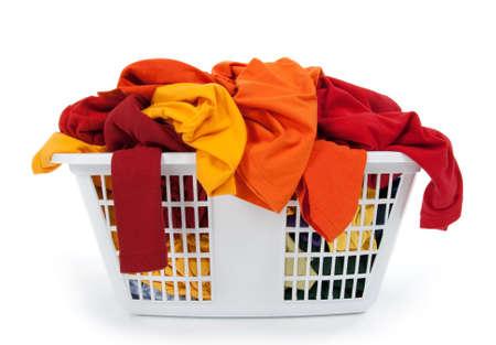lavanderia: Ropas coloridas en una canasta de lavander�a sobre fondo blanco. Rojo, naranja, amarillo.  Foto de archivo