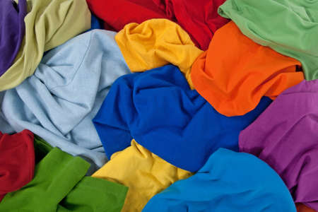 heap: Close-up of a messy pile of colorful clothing, abstract background.