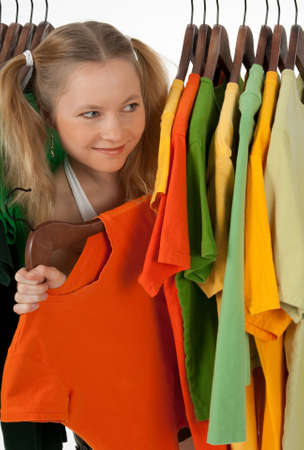 Curious girl looking out of the clothes rack in a store, choosing what to buy. Stock Photo - 8189040