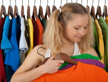 Girl standing near the rack of colourful clothing, choosing clothes to buy. photo