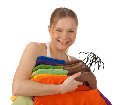 Charming young woman holding lots of colourful clothes on hangers. Isolated on white.