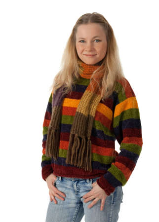 Smiling young woman wearing striped sweater and scarf, holding hands in pockets. photo