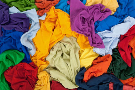mess: Lots of bright messy colorful clothing, abstract background.