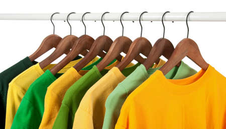 Choice of green and yellow shirts and t-shirts on wooden hangers, isolated on white.