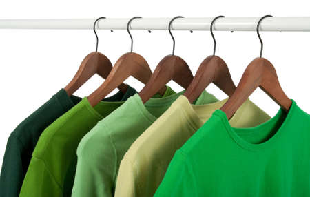 Choice of casual shirts on hangers, different tones of green. Isolated on white. photo