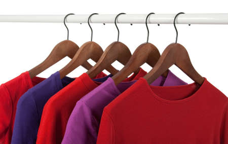 Choice of red and purple casual shirts on wooden hangers, isolated on white.