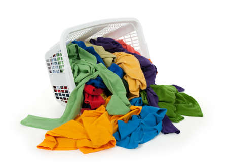 messy clothes: Bright colorful clothes falling out of a laundry basket. Isolated on white background.