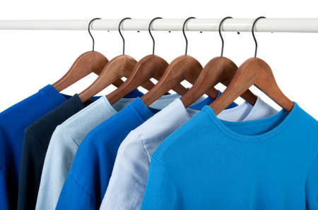 Choice of casual shirts on hangers, different tones of blue. Isolated on white.