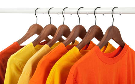 Choice of yellow and orange casual shirts on wooden hangers, isolated on white. photo
