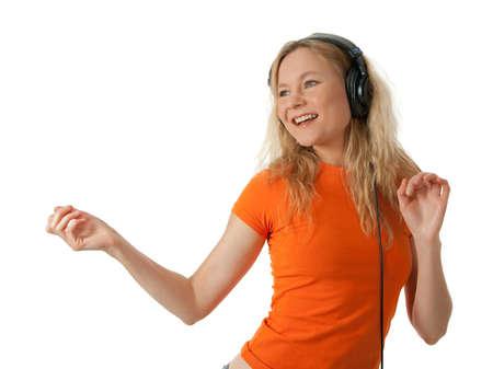Happy girl in orange t-shirt, listening to music in headphones and dancing.