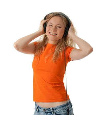 Smiling happy girl in orange t-shirt, listening to music in headphones. Stock Photo - 8398201