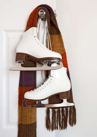 ice skating: Elegant white figure skates and colourful scarf hanging on a door knob. Stock Photo