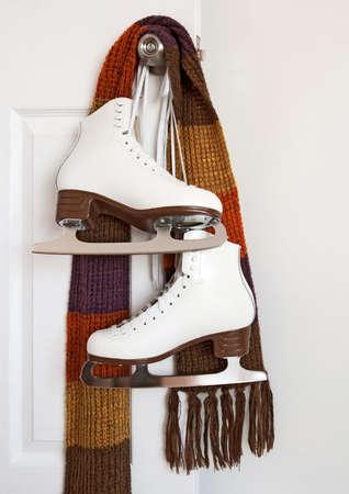 patinaje: Patines figura blanco elegante y colorido bufanda colgado en un pomo de la puerta.