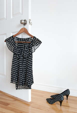 Black and white polka dot blouse on a hanger and shoes on wooden floor.