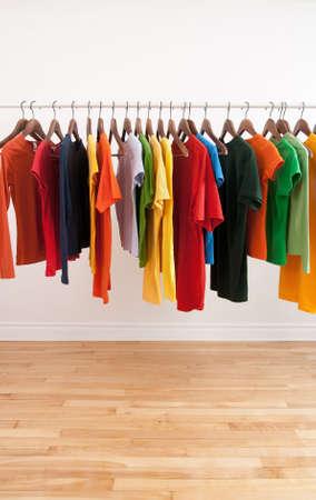 ropa colgada: Variedad de multicolor ropa informal en una varilla, en una sala de brillante.