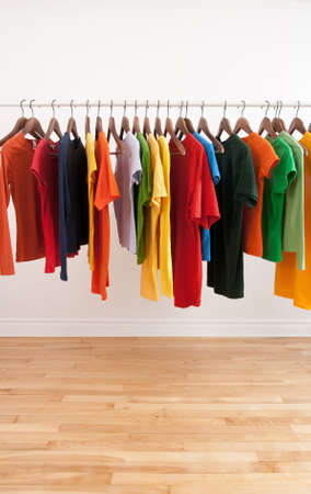 Variety of multicolored casual clothes on a rod, in a bright room. photo