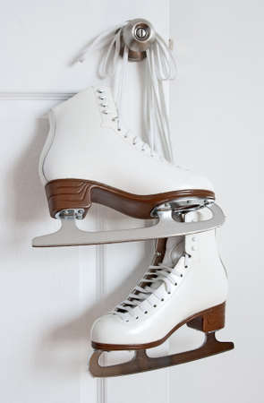 figure skates: Elegant white figure skates hanging on a door knob.