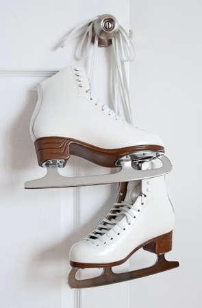 patinaje sobre hielo: Patines de elegante figura blanco colgado en un pomo de la puerta.
