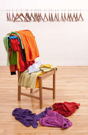 mess: Colorful messy clothes on a chair and row of empty hangers on the background.
