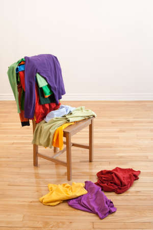 messy clothes: Lots of colorful messy clothes on a chair and on a wooden floor. Stock Photo