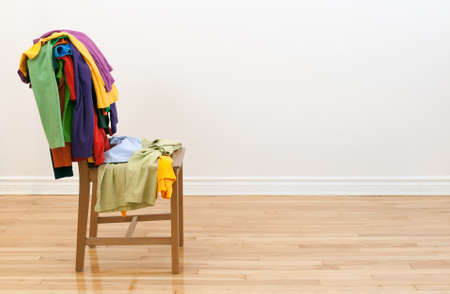 messy clothes: Wooden chair in a room, with lots of colorful messy clothes on it.