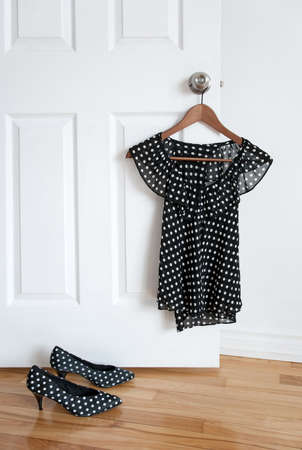 Black and white polka dot shoes and stylish blouse on a hanger.