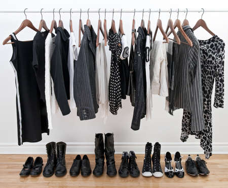 gray clothing: Female black and white clothes on a pole and shoes on a wooden floor. Stock Photo