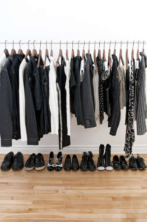 womens clothing: Black and white clothes on a pole and shoes on a wooden floor.