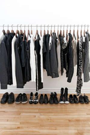 Zwart-wit kleding op een paal en schoenen op een houten vloer.