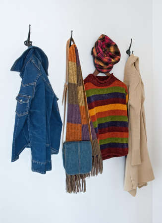 coat rack: Colorful clothing and bag on metal coat hooks, on a white wall.