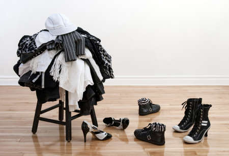 Heap of black and white clothes on a stool and disordered shoes on a wooden floor.