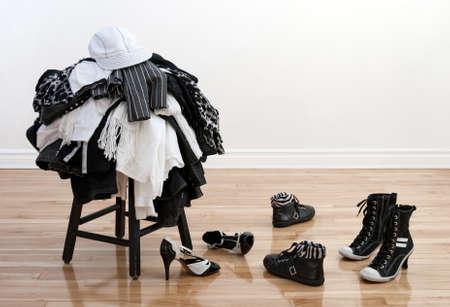 disordine: Mucchio di vestiti di bianchi e nero su uno sgabello e disordine scarpe su un pavimento di legno.