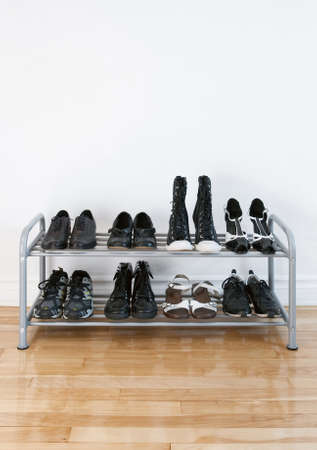 Shoe rack with black shoes and boots, on a wooden floor, besides a white wall.