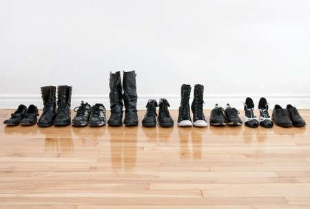 to row: Fila de zapatos negros y botas sobre un suelo de madera, delante de una pared blanca.