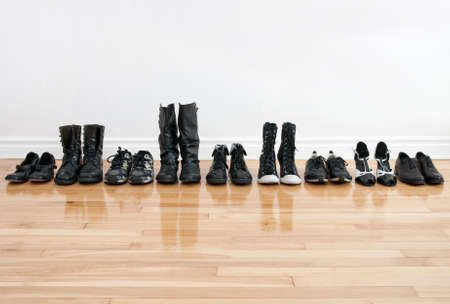 shoes fashion: Row of black shoes and boots on a wooden floor, in front of a white wall.