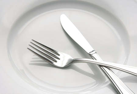 Closeup of shiny fork and knife on a white plate. photo