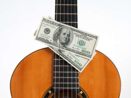 Money put between the chords of a classical guitar. photo
