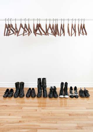 Rij van zwarte schoenen en laarzen op een houten vloer, en lege hangers op een staaf. Stockfoto