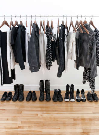 coat rack: Black and white female clothes on hangers and shoes on a wooden floor.