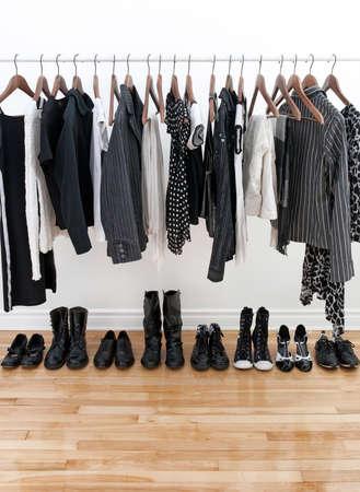 Zwart-wit vrouwelijke kleding op hangers en schoenen op een houten vloer.