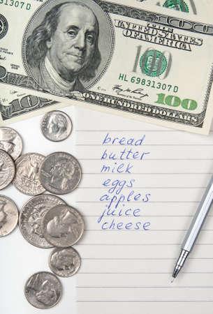 write us: Cost of living. Money, pen and handwritten shopping list.