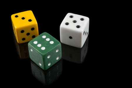 Green, yellow and white dices with reflection on black background. photo