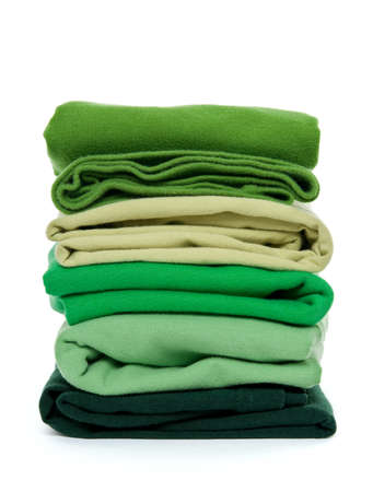 Laundry - pile of green folded clothes on white background.
