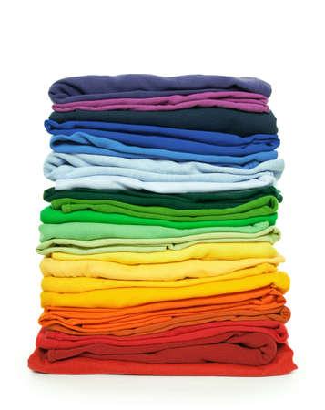in a pile: Lavander�a de arco iris. Pila de ropa plegada brillante sobre fondo blanco.