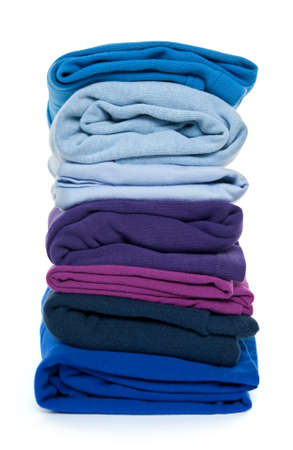 Fresh laundry. Pile of blue and purple folded clothes on white background.