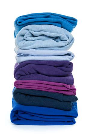 Fresh laundry. Pile of blue and purple folded clothes on white background. photo