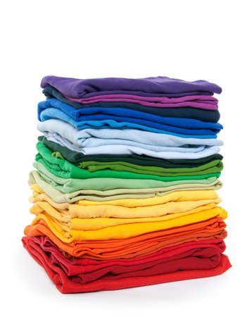fold: Rainbow clothes pile. Bright folded clothes on white background.